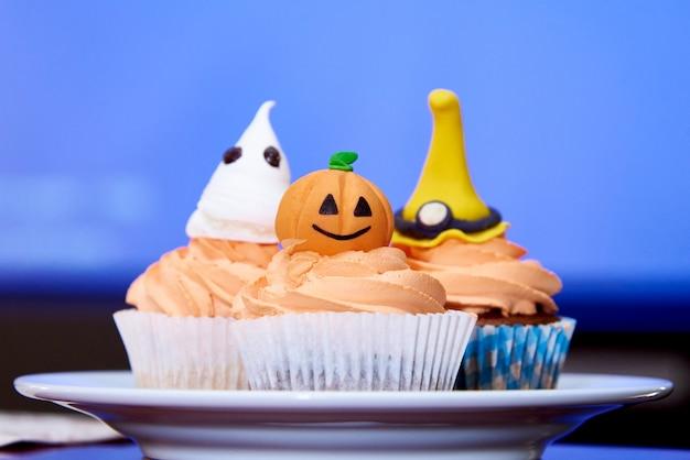 Cupcake pumpkin for halloween on blue Premium Photo