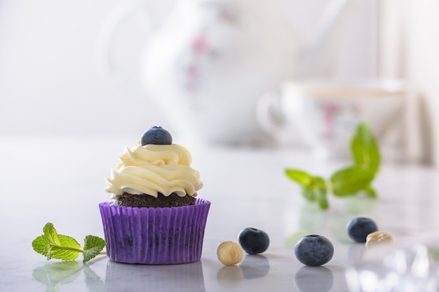 Cupcake with blueberry and hazelnut in purple wrap on white natural marble desk. Premium Photo