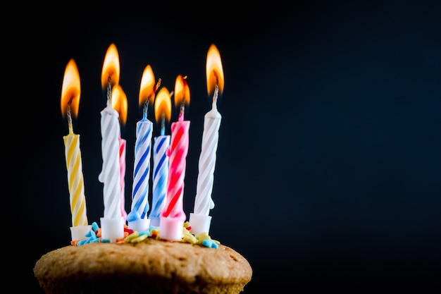 Cupcake with burning festive candles on a black background Premium Photo