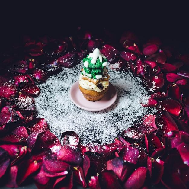 バラの花びらの輪の上に立つ釉薬の冬の木を持つカップケーキ 無料写真
