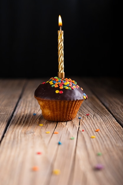 Cupcake with glaze and lit candle Free Photo
