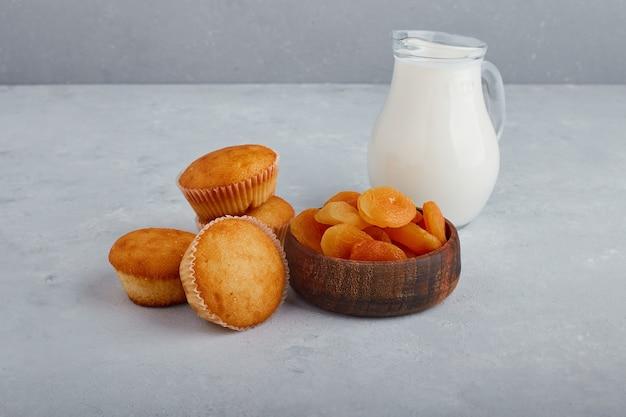 灰色の背景に牛乳の瓶とカップケーキとドライアプリコット。 無料写真