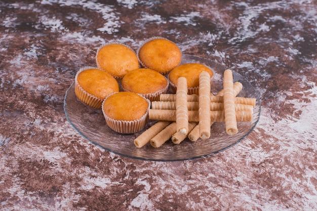Кексы и вафельные палочки в стеклянном блюде Бесплатные Фотографии