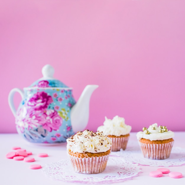 Cupcakes; candies and teapot on white surface Free Photo