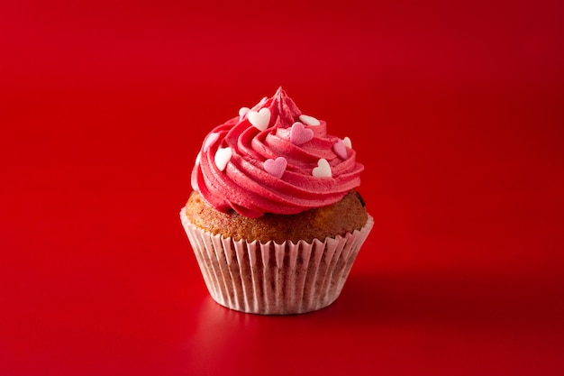 Cupcakes decorated with sugar hearts for valentine's day on red background Premium Photo