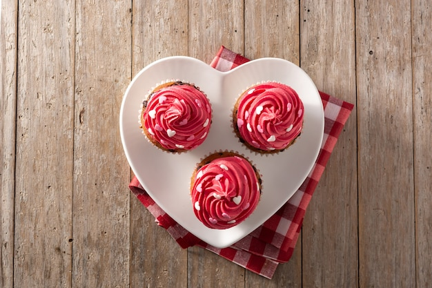 Cupcakes decorated with sugar hearts for valentine's day on wooden table. top view Premium Photo
