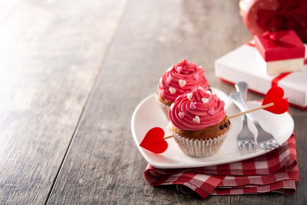 Cupcakes decorated with sugar hearts for valentine's day on wooden table Premium Photo