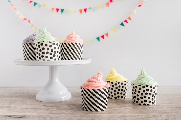 Cupcakes pastel color buttercream in front of pennant Free Photo