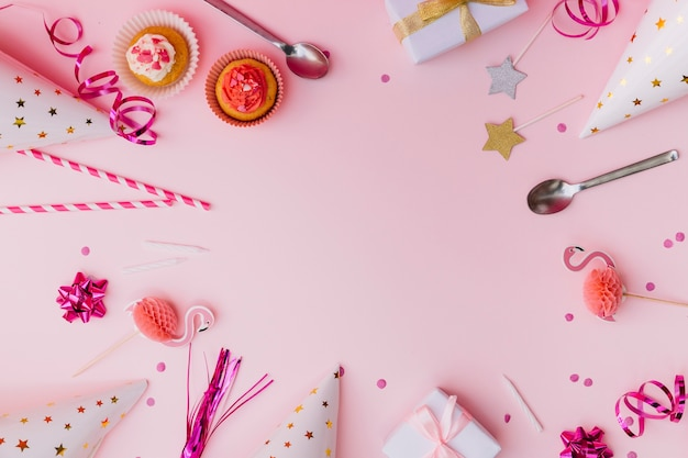 Cupcakes; streamer; drinking straws; prop; spoon; candle; gift boxes; confetti and party hat on pink background Free Photo