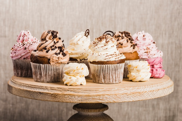 Cupcakes and whipped creams on wooden stand Free Photo