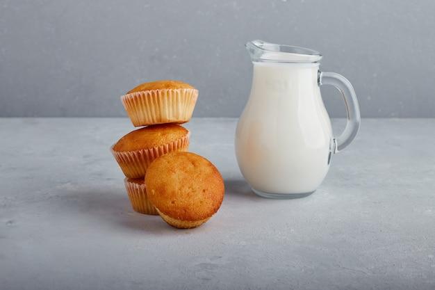 灰色の背景に牛乳の瓶とカップケーキ。 無料写真
