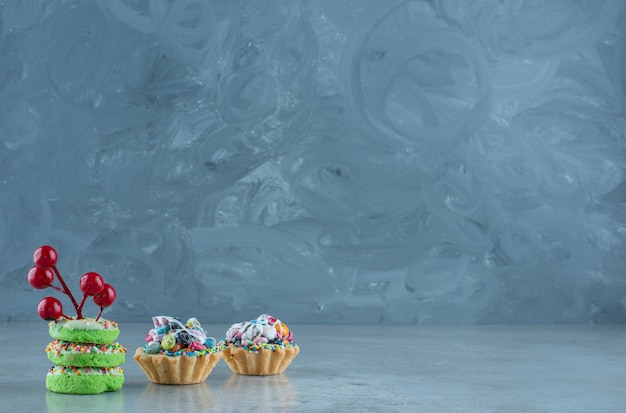 Cupcakes with candy fillings and small donuts on marble background. high quality photo Free Photo