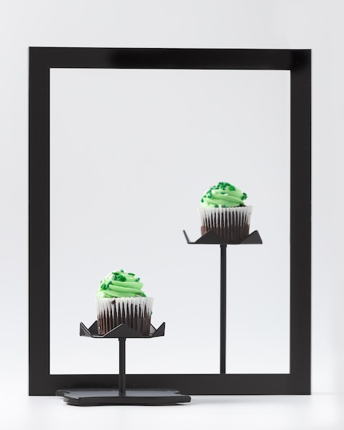 Cupcakes with green creme on black frame Free Photo