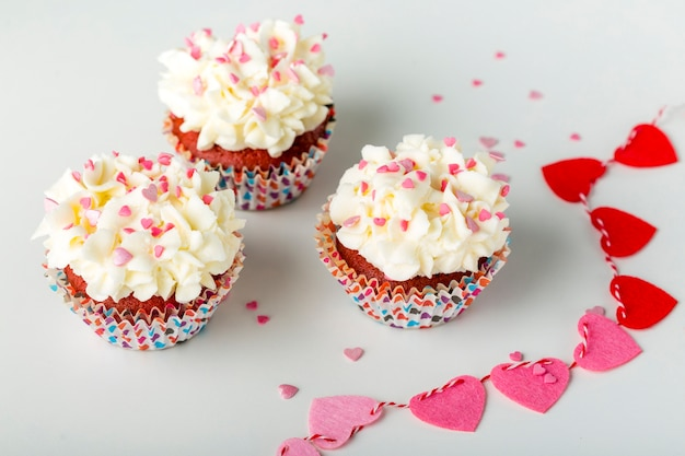 Cupcakes with heart-shaped sprinkles and frosting Free Photo