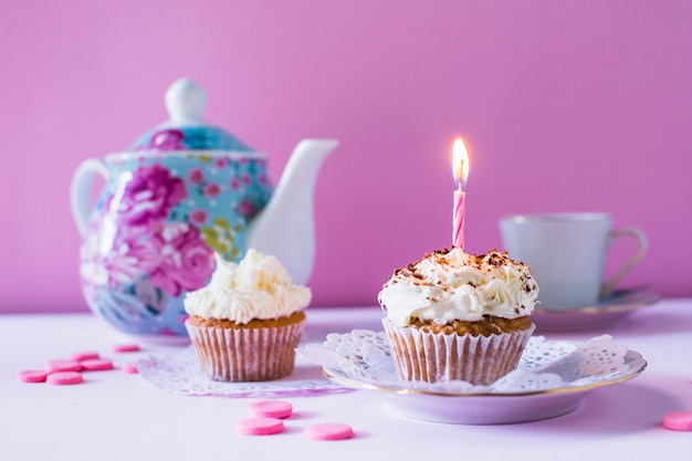 Cupcakes with illuminated candle on table top Free Photo