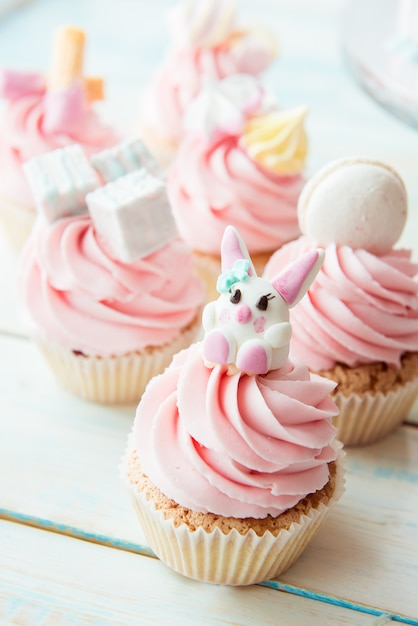 ピンクのクリームで飾られたカップケーキバニー、マシュマロ、マカロン Premium写真