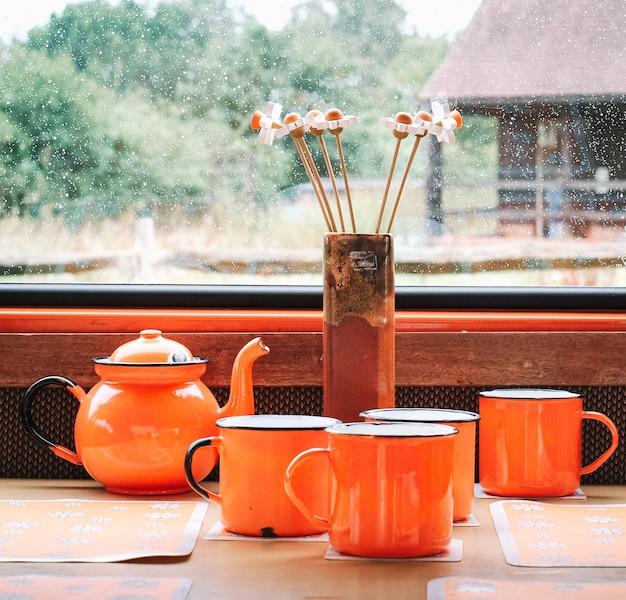 雨の日の窓の前の花の横にあるカップとティーポット 無料写真