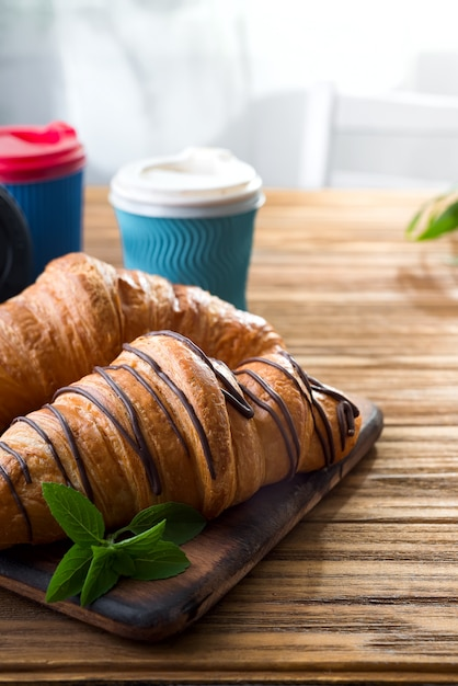 Cups of coffee and two croissants on the street in croissant cafe Premium Photo
