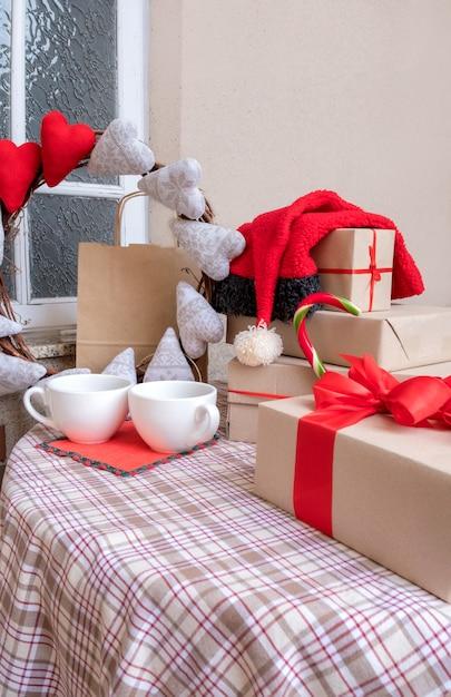집에서 축제 테이블에 커피, 하트, 쇼핑백 및 선물 컵. 프리미엄 사진