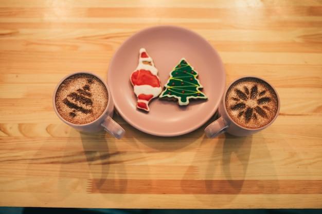 クリスマスのジンジャーブレッドが付いているプレートの両面にコーヒーが付いているカップ 無料写真