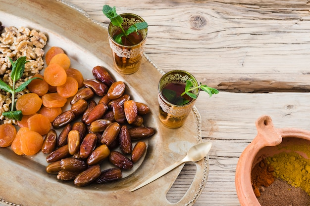 Cups with plant twigs near bowl with spices and dried fruits and nuts on tray Free Photo