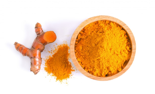 Curcuma powder in a bowl and root on white background Premium Photo