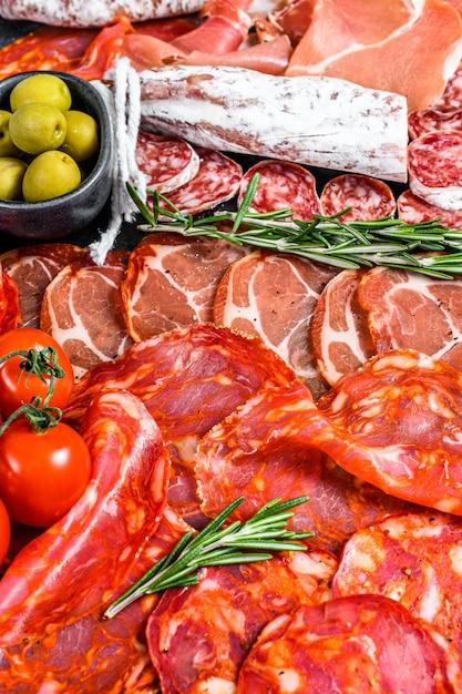 Cured meat platter of traditional spanish tapas. chorizo, jamon serrano, lomo and fuet. top view. Premium Photo