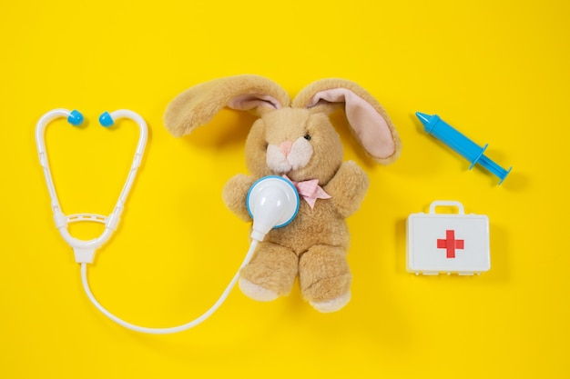 Curing a rabbit. toy medical devices on a yellow. Premium Photo