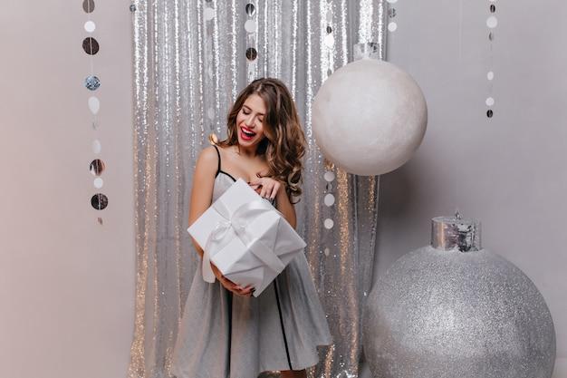 Любопытная шатенка в платье партии, держащей подарочную коробку. улыбающаяся беззаботная девушка с подарком стоит возле больших елочных игрушек. Бесплатные Фотографии