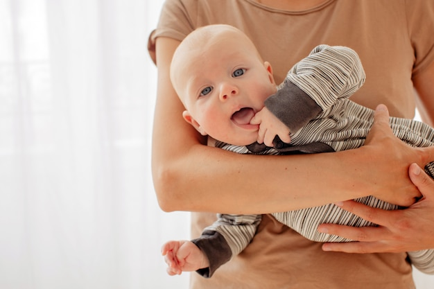 母親の手に好奇心が強い生意気な赤ちゃん Premium写真