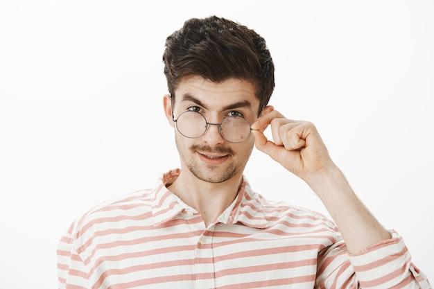 素晴らしいことをじっと見つめる好奇心旺盛なハンサムな男。ひげと口ひげで満足している魅力的な男性、額の下から見て、眼鏡を外して、灰色の壁越しに興味を持って満足 無料写真
