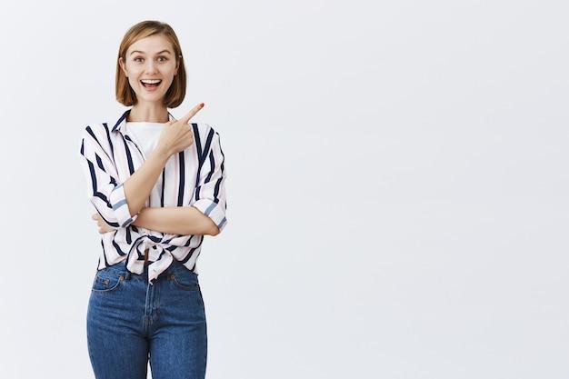 Curiosa e intrigata ragazza attraente spot interessante promo, indicando l'angolo in alto a destra Foto Gratuite