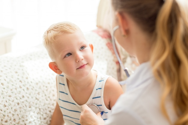 Curious little boy looking at female doctor Free Photo
