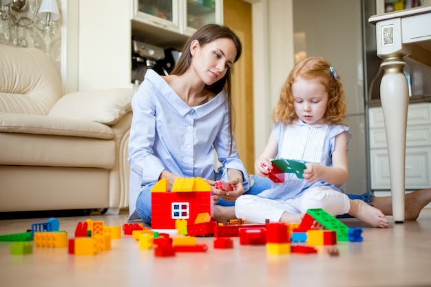 Curious little girl and mother playing together Premium Photo