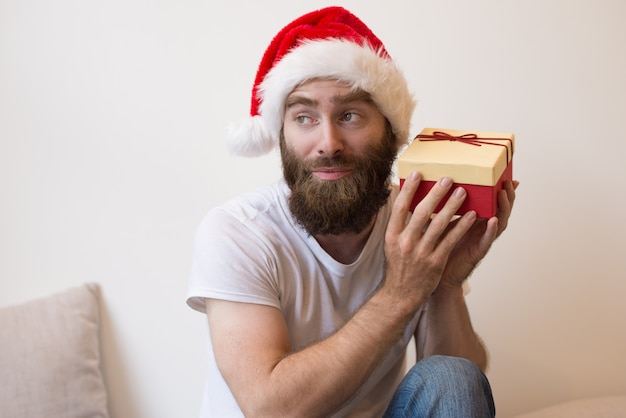 Curious man trying to guess what is inside christmas gift box Free Photo