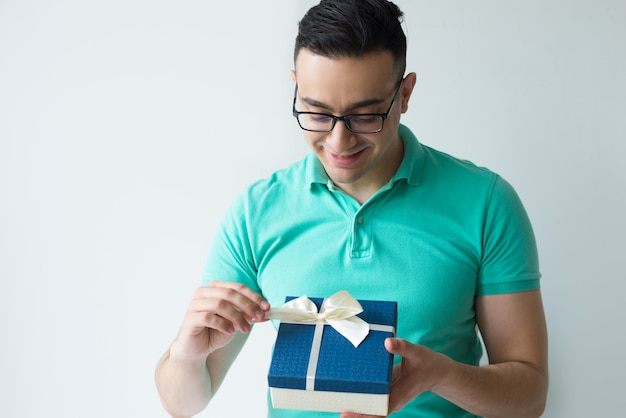 Curious man wearing polo t-shirt and unwrapping gift box Free Photo