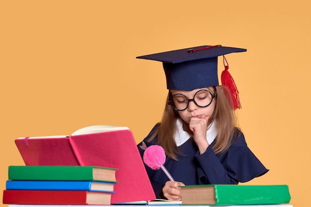 Curious schoolgirl in graduation outfit studying with textbooks Premium Photo