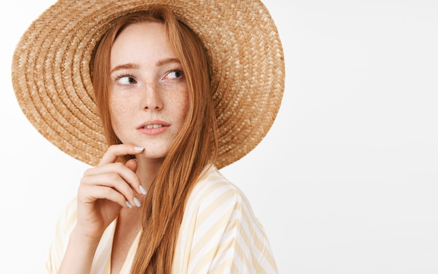 Любопытная задумчивая очаровательная рыжая девочка с милыми веснушками в модной летней соломенной шляпе поворачивает направо и с интересом смотрит и заинтригованно трогает подбородок, размышляя и наблюдая Бесплатные Фотографии