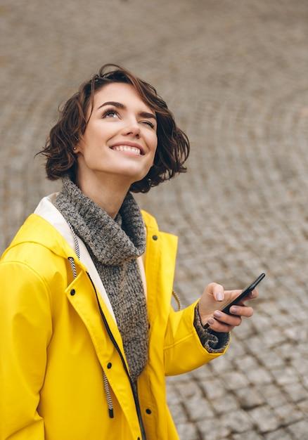 スマートフォンで予報を読んで、彼女の目を台無しに空を見ている茶色の巻き毛を持つ好奇心が強い女性 無料写真