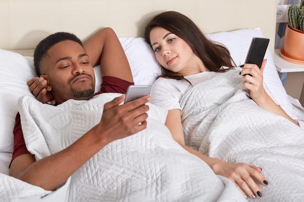 Любопытная молодая европейка смотрит на экран смартфона своего темнокожего парня, который общается с друзьями, испытывает ревность, остается вместе в постели во время выходных или выходных. концепция отношений Premium Фотографии