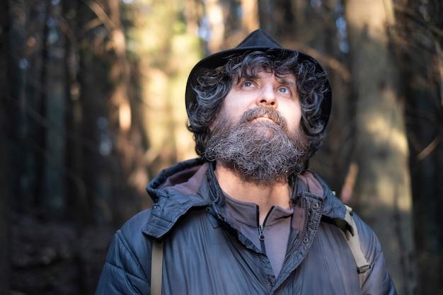 公園や森の帽子のひげと青い目を持つ巻き毛の大人ブルネット男性 Premium写真