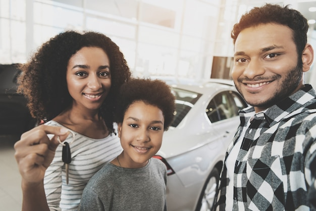 Curly afro woman holds keys family purchasing car. Premium Photo
