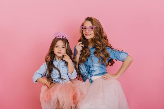 Кудрявая красивая девушка с фиолетовой короной позирует рядом с молодой привлекательной матерью, держащей маскарадную маску на розовом фоне. очаровательная женщина в винтажном наряде весело с дочерью на дне рождения. Бесплатные Фотографии