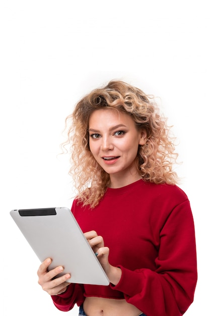Curly blonde girl with on tablet on white Premium Photo
