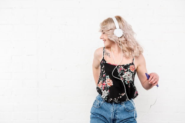 Curly blonde woman in headphones listening to music and dancing Free Photo