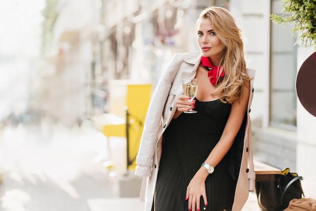 シャンパンで何かを祝う黒いプリーツドレスの巻き毛のブロンドの女性。ワインのグラスを保持している嬉しい金髪の少女の屋外の肖像画。 無料写真