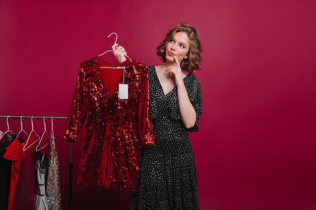 Кудрявая шатенка с милым личиком нашла стильное платье и задумалась о покупке. крытый портрет прекрасной европейской леди, стоящей в магазине одежды с вешалкой в руке. Бесплатные Фотографии