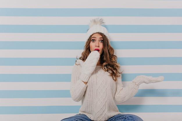 驚きの巻き毛の暗いブロンドの女の子は彼女の手で顔を覆います。白いニットセーターの女性の肖像画 無料写真