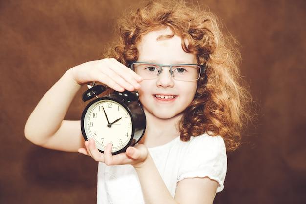Curly girl holding alarm clock. Premium Photo