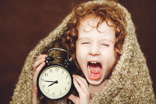 Curly girl  yawn and holding alarm clock. Premium Photo